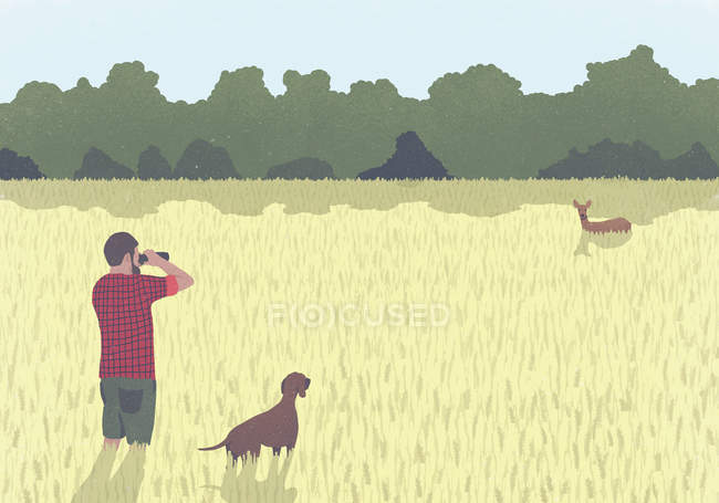 A man with binoculars and dog standing in field looking at wild deer — Stock Photo