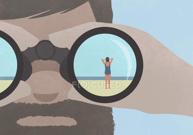 Riflessione della donna in piedi sulla spiaggia in binocolo tenuto da un uomo con la barba — Foto stock