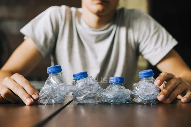 Adolescent garçon recyclage plastique bouteilles d'eau — Photo de stock