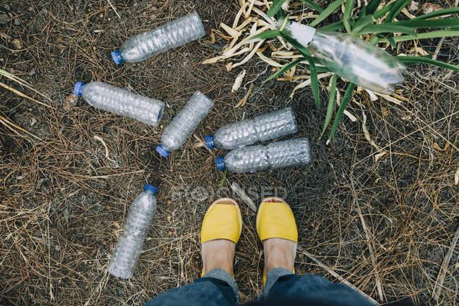 Perspective personnelle femme debout à des bouteilles d'eau en plastique jonché — Photo de stock