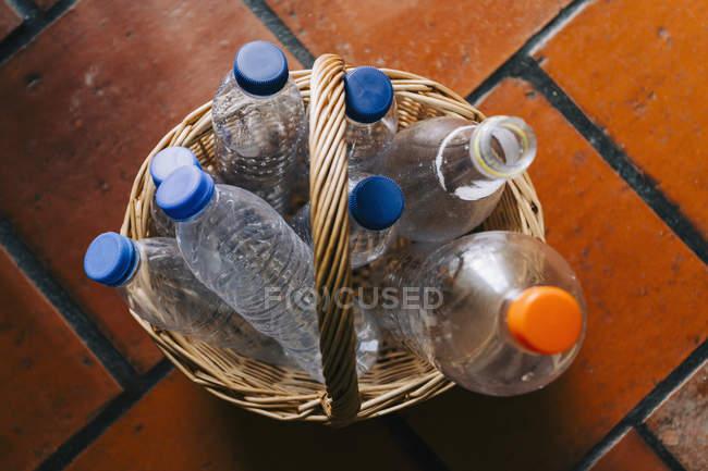 Bouteilles d'eau en plastique recyclées dans le panier — Photo de stock