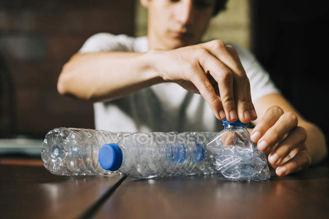 Teenage boy recycling water bottles — Stock Photo