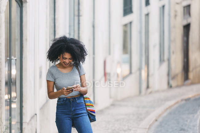 Young woman using smart phone on urban street — Stock Photo