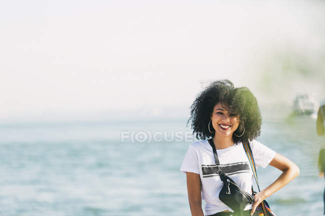 Porträt einer lächelnden jungen Frau am Meer — Stockfoto