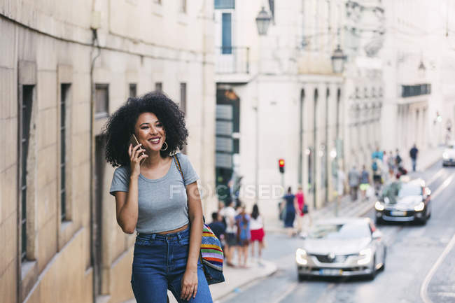 Smiling young woman talking on smart phone on urban street, Lisbon, Portugal — Stock Photo