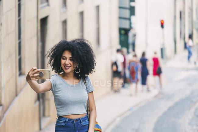 Jovem com telefone inteligente tirando selfie na rua urbana — Fotografia de Stock