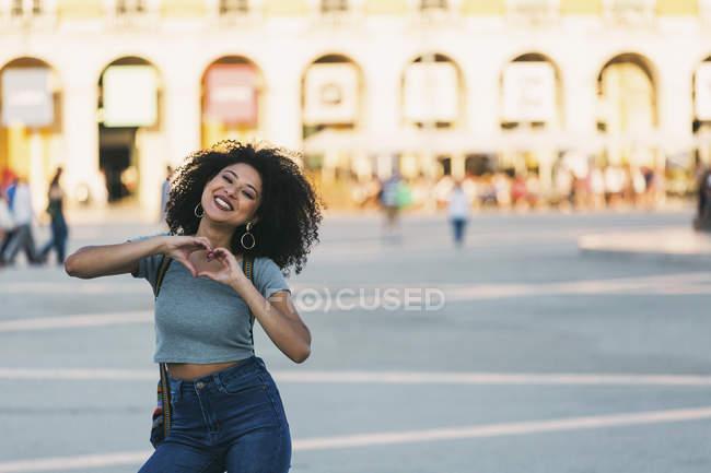 Ritratto giovane donna entusiasta che forma a forma di cuore con le mani in Praca do Comercio, Lisbona — Foto stock