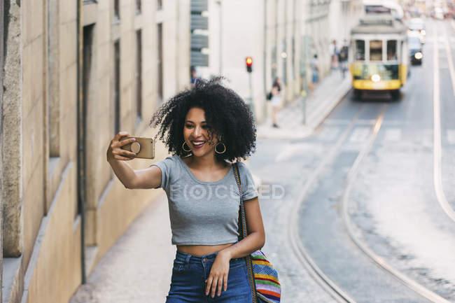 Giovane donna con smart phone scattare selfie sulla strada urbana — Foto stock