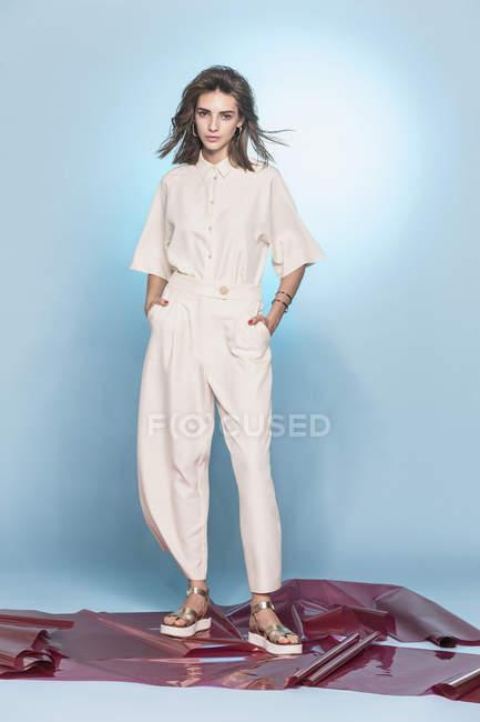 Portrait of female fashion model posing against blue background — Stock Photo