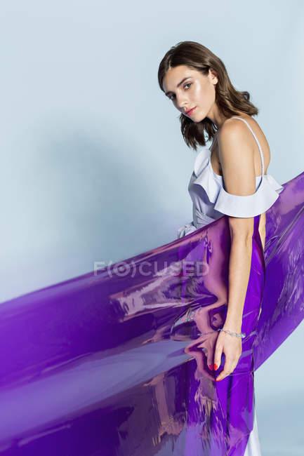 Porträt eines weiblichen Modells, das in lila Plastikfolie vor blauem Hintergrund gehüllt ist — Stockfoto