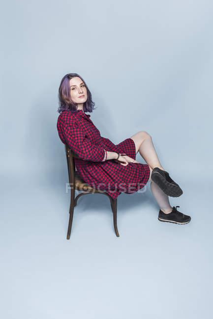 Портрет впевнено і модно молода жінка сидить на стільці синій тлі — стокове фото