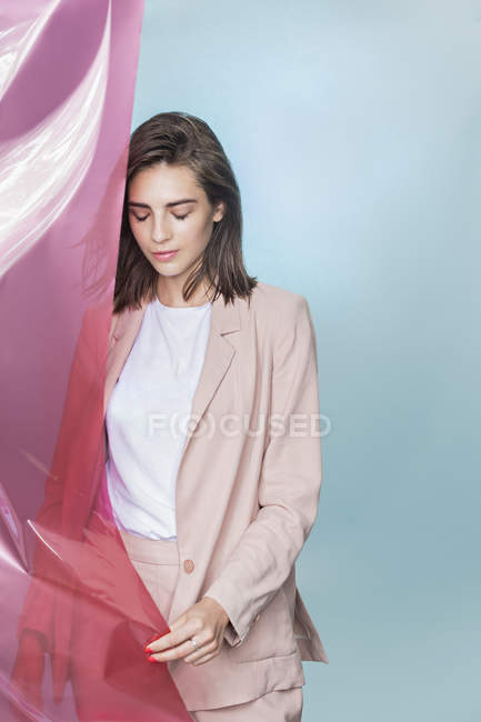 Portrait of a female fashion model posing with pink fabric and looking down — Stock Photo