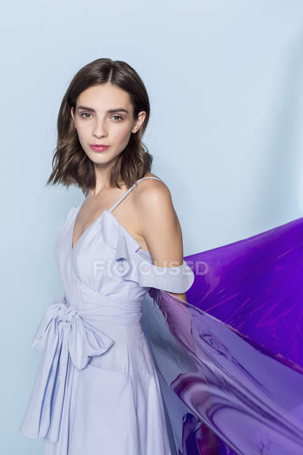 Portrait of a female fashion model posing with purple plastic sheet against blue background — Stock Photo