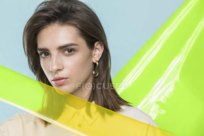 Portrait d'un mannequin féminin posant avec des feuilles de plastique jaune — Photo de stock