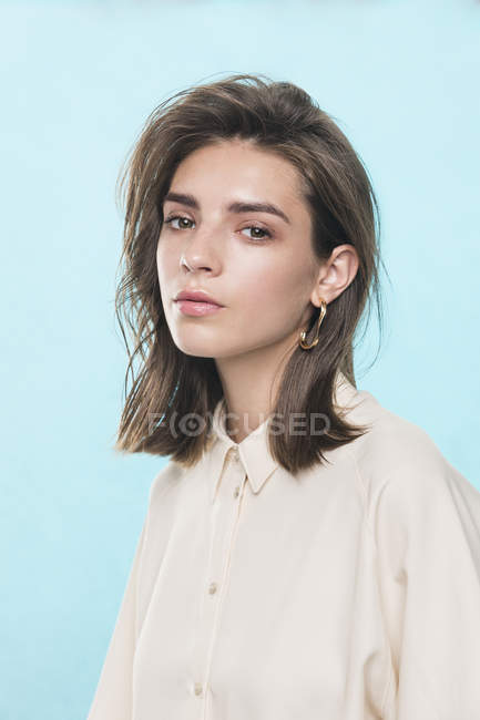 Portrait of female fashion model against blue background — Stock Photo