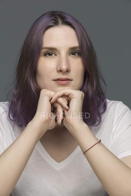 Retrato de uma jovem mulher com cabelos tingidos e queixo descansando nas mãos contra fundo cinza — Fotografia de Stock