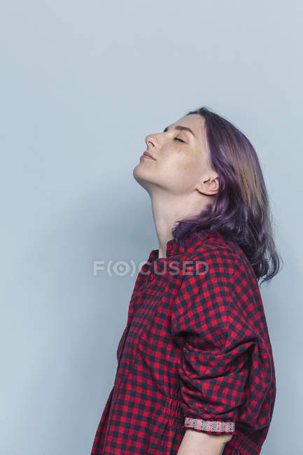 Side portrait of young woman with dyed hair and eyes closed against gray background — Stock Photo