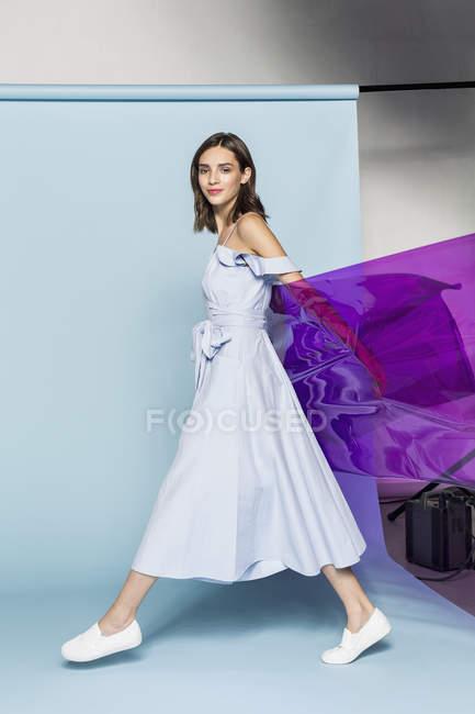 Porträt eines weiblichen Models, das mit lila Plastikfolie vor blauem Hintergrund posiert — Stockfoto