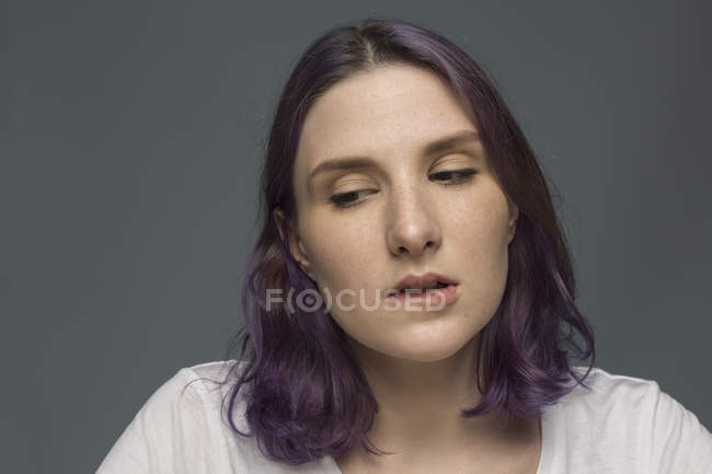 Portrait of young woman with dyed hair and biting lip — Stock Photo