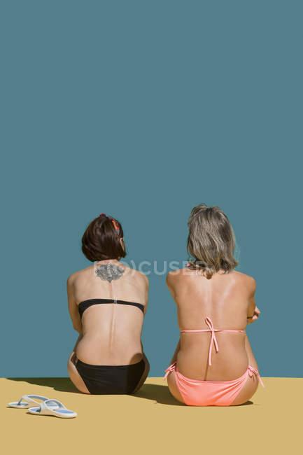 Frauen in Bikinis sonnen sich auf grünem Hintergrund — Stockfoto