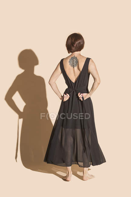 Frau mit Rücken-Tätowierung, die schwarzes Kleid bindet — Stockfoto