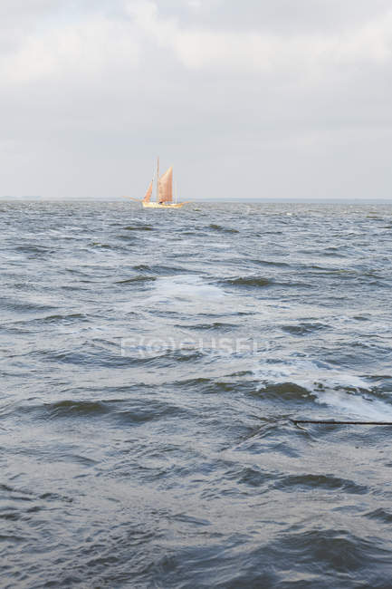 Sailboat on choppy ocean — Stock Photo