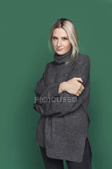Portrait of woman with blond hair and wearing gray turtleneck sweater — Stock Photo