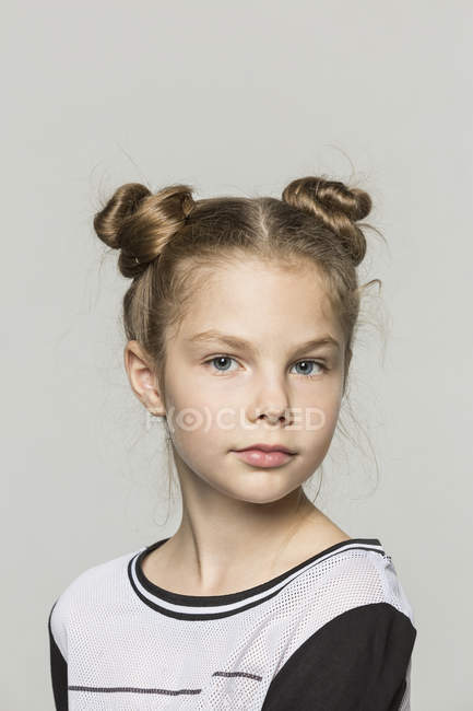 Portrait of young girl with double hair buns against grey background — Stock Photo