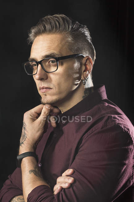 Portrait of serious man wearing glasses and looking away against black background — Stock Photo