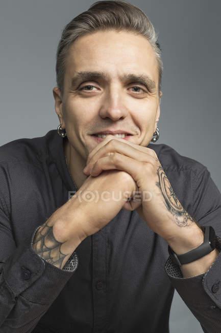 Портрет людина посміхається і відпочиваючи підборіддя на руки на сірому тлі — стокове фото