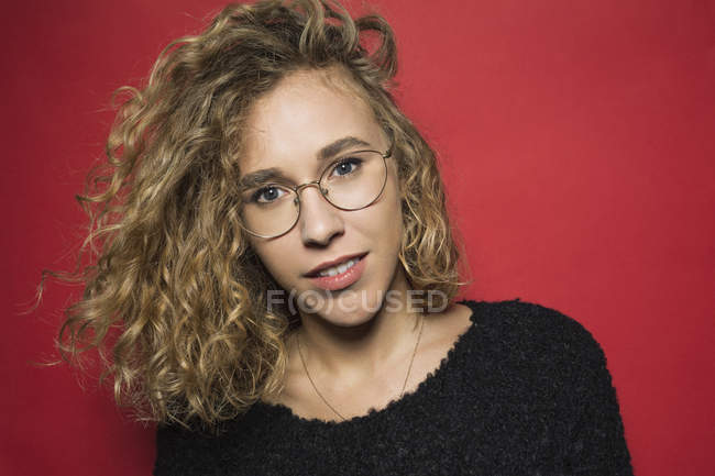 Portrait of woman with curly hair and wearing glasses against red background — Stock Photo