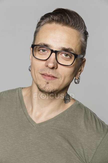 Portrait d'un homme avec des lunettes sur fond gris — Photo de stock