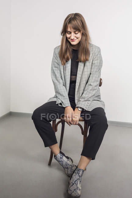 Portrait of stylish woman with long brown hair sitting on chair — Stock Photo