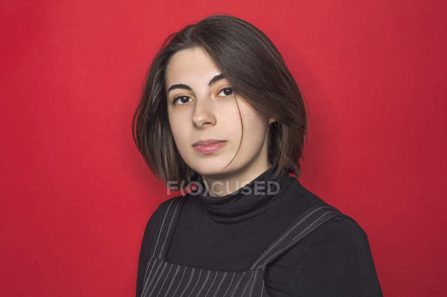 Portrait of woman with dark hair and serious expression against red background — Stock Photo