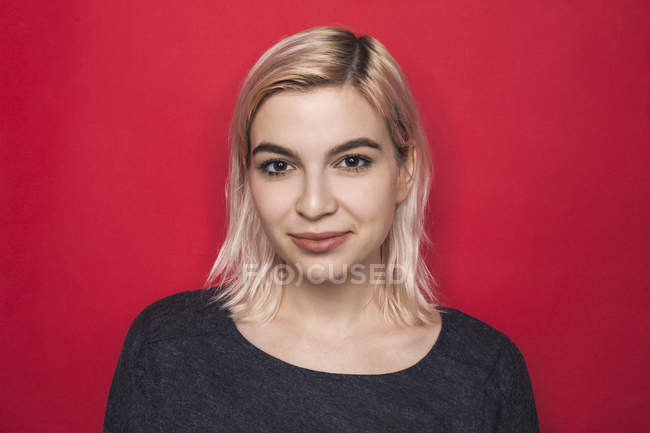 Portrait of woman with bleached hair and smiling against red background — Stock Photo