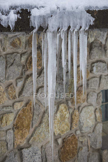 Icicles hanging over stone house roof — Stock Photo