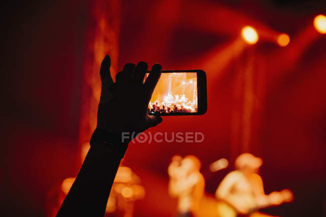 Hand in audience video recording musical concert with camera phone — Stock Photo