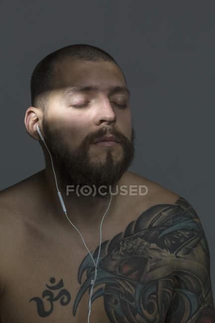 Голый мужчина с бородой и татуировками слушает музыку с наушниками — стоковое фото
