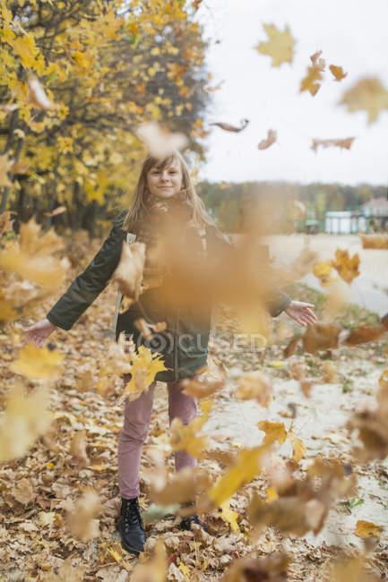 Verspieltes Mädchen spielt im Herbstlaub im Park — Stockfoto