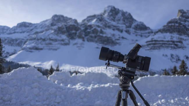 Video cámara en el trípode debajo del paisaje de montaña cubierto de nieve, Banff, Alberta, Canadá - foto de stock