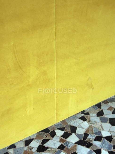 Mosaic tile below vibrant, yellow wall — Stock Photo