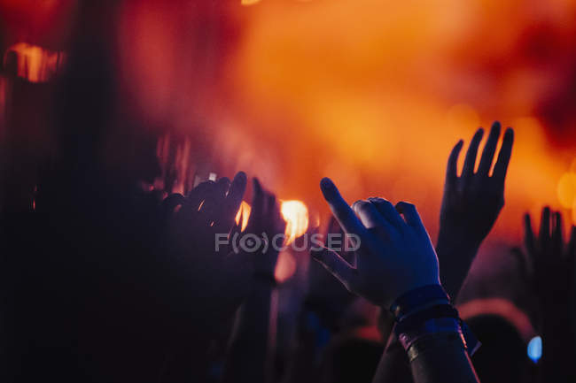 Hands raised, cheering in concert audience — Stock Photo
