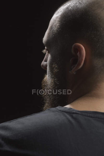 Profile of serious man with beard and earring — Stock Photo