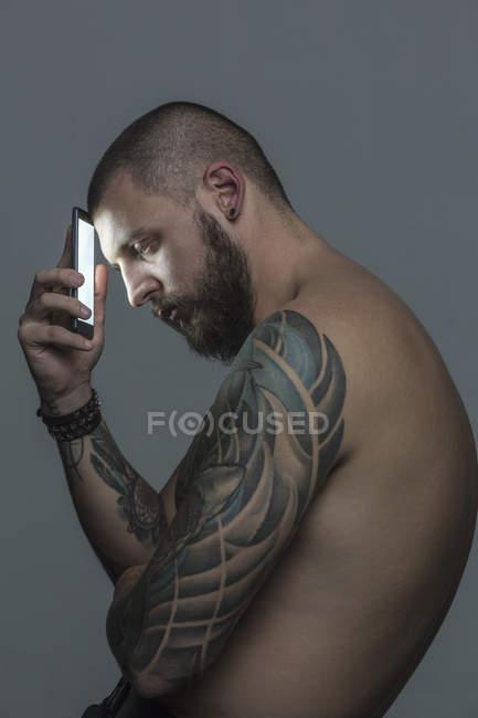 Retrato de un hombre serio y desnudo con tatuajes que sostiene teléfonos inteligentes. - foto de stock