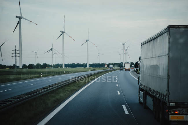 Trucks and cars moving on highway along wind turbines, Brandenburg, Germany — Stock Photo