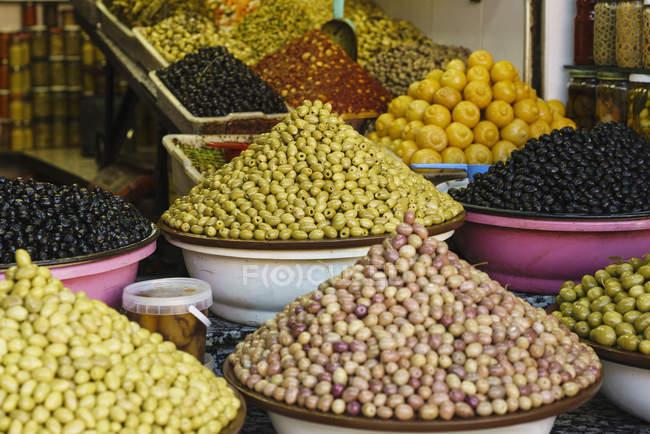 Abundante variedad de aceitunas frescas en exhibición en tienda zoco, Marrakech, Marruecos - foto de stock