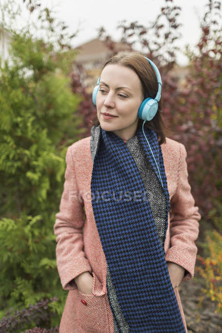 Woman in scarf and coat listening to music with headphones — Stock Photo