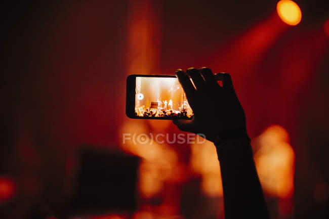 Hand of man in audience video recording concert with camera phone — Stock Photo