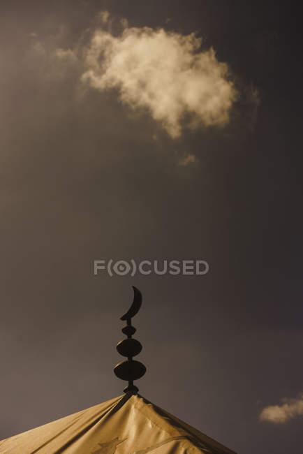 Símbolo da lua crescente do Islã em cima Mesquita abaixo céu tempestuoso, Marraquexe, Marrocos — Fotografia de Stock