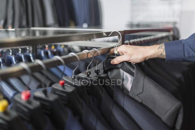 Людина досягає костюм на вішалці в магазин чоловічого одягу — стокове фото
